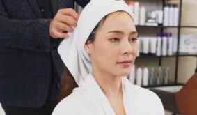 Professional male stylist using hair towel wrap woman's hair after washing in beauty salon shop.