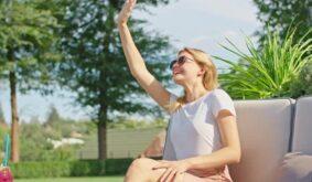 Beautiful Young Woman in a White Tshirt Waving Her Hand to Someone Enjoying a Wonderful Hot Summer