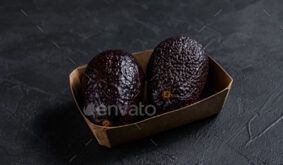Avocado in a cardboard package from the supermarket. Black background. Top view. Space for text