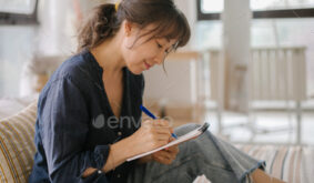 Asian woman making notes in notebook, working at home on bed in cozy bedroom. Concept of freelancer