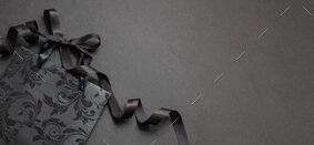 Black Friday concept. Black shopping bag on black background.
