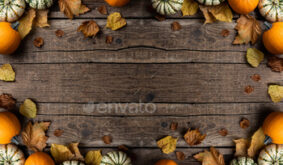 Autumn composition from pumpkins and autumn leaves on wooden background