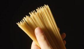A gourmet (expert) hand touch a pile of a spaghetti